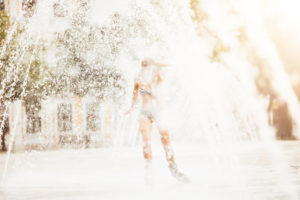 Young woman travels with inline skates through a fountain