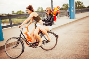 Two women driving on a bike and enjoy the summer