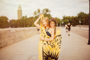 Two young women standing in a blanket wrapped on bridge