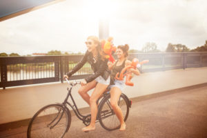 Two young women ride with a bike through the city,