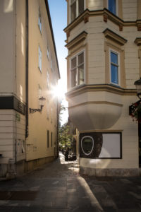 Sun shines between two houses in Ljubljana's city center