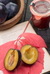 aufgeschlagenes Buch, Herbstblatt, Pflaumen und eingewecktes Pflaumenkompott