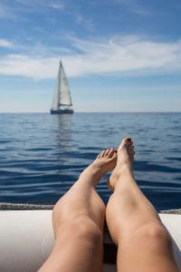 Ich-Perspektive, Blick auf Beine, die über den Rand eines Schlauchbootes auf dem Meer hängen