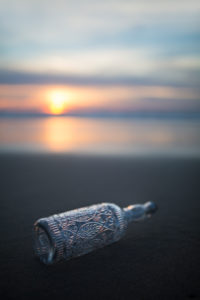Glass bottle with decorations on the beach in the evening light