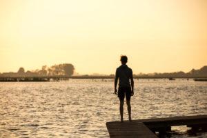 Junger Mann auf einem Steg im Sonnenuntergang
