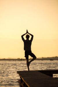 Junger Mann macht Yoga auf einem Steg am See