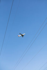 Flugzeug am Himmel, darunter: Stromkabel