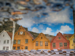 Houses reflecting in a puddle in Bergen, Norway, historic row of houses at the harbor, Tyske Brygge in Bergen, Norway