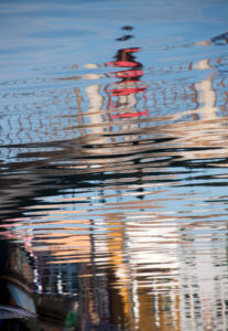 Facades of houses reflected in the water on the island of Burano in the lagoon of Venice, Italy