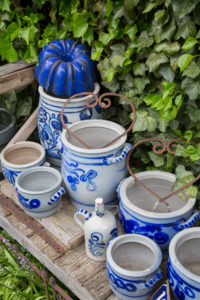 Old  wooden bench, stoneware pots and bellarmines in the garden