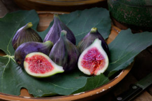 Ripe figs with leaves in terracotta bowl
