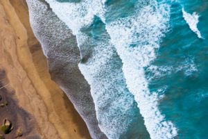 Waves on sandy beach, Playa Famara at Caleta de Famara, drone shot, Lanzarote, Canary Islands, Spain