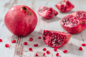 Whole pomegranate and pomegranate pieces on white wooden table