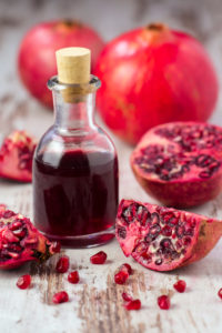Glass bottle with pomegranate juice and pomegranates