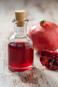 Glass bottle with pomegranate juice and pomegranate