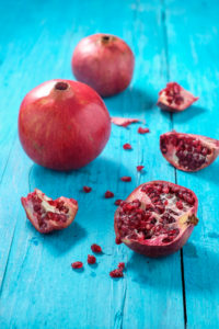 Whole and sliced pomegranates on turquoise wooden table