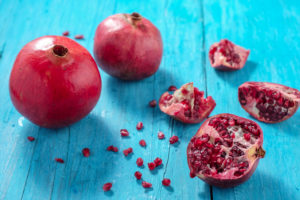 Whole and cut pomegranates on turquoise wooden table
