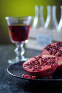 Still Life with sliced pomegranate, glass with pomegranate juice and bottle