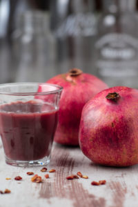 Two pomegranates and glass with pomegranate juice, close-up