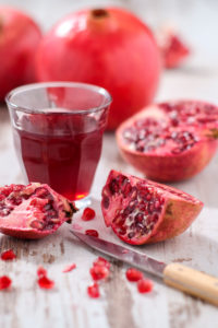 Whole and sliced pomegranates, knives, glass with pomegranate juice
