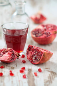 Sliced pomegranates, seeds and glass with pomegranate juice