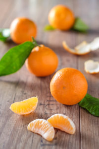 clementines with foliage, pieces of clementines and peel on a wooden table