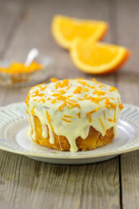 Small orange cake with white icing on plate
