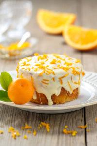 Kleiner Orangenkuchen mit weißer Glasur auf Teller