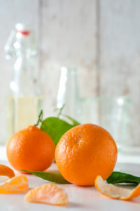 clementines with foliage, pieces of clementines and peel in front of bright background,