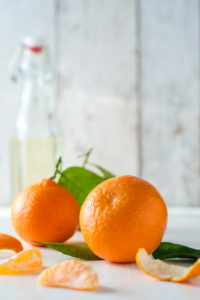 clementines with foliage, pieces of clementines and bowl in front of bright background,