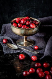 Still life with fresh red Cranberries in an old silver bowl in front of dark background