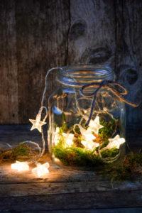 Weihnachtliches Stillleben mit Lichterkette in einem rustikalen Glas