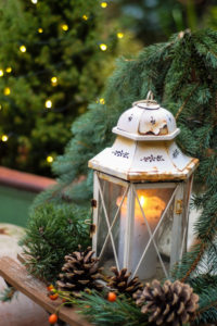 Christmassy decoration with lantern, cone and fir branches on terrace,
