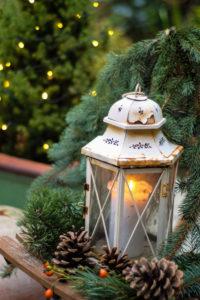 Weihnachtliche Dekoration mit Laterne, Zapfen und Tannenzweigen auf Terrasse,