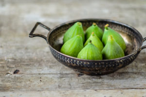 Fresh green figs in an old metal bowl on an old wooden table