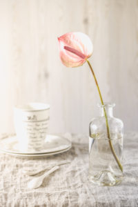 Still life with pink anthurium in a glass vase on table with bright linen cloth and tableware