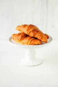 Weißer Tortenständer mit frischen Croissants