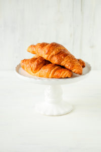 White cake stand with fresh croissants
