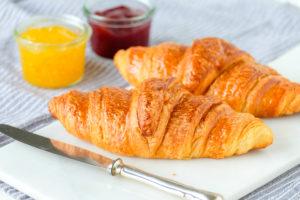 Close-up frische Croissants und Konfitüre zum Frühstück