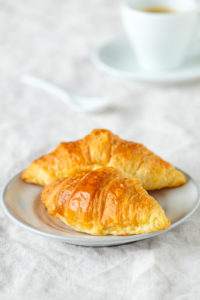Fresh croissants on a brightly covered breakfast table