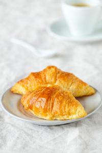 Frische Croissants auf einem hell gedeckten Frühstückstisch