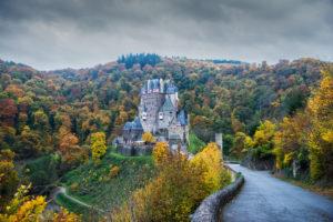 Frontal view, Burg Eltz, autumnal Eifel landscape with dark clouds.
