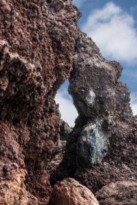 Volcanic rock with a natural window with a view of the sky.