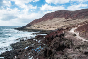 Coast and volcanic landscape at Montana Roja on Tenerife in slightly cloudy sky