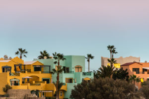 Colorful housing complex with palm trees in front of a evening sky at the coast of Tenerife.