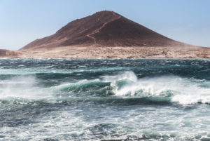 The volcano Montana Roja on Tenerife with the storm-lashed bay of El Medano in the foreground.