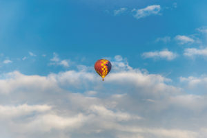 Colorful, flying hot air balloon in front of cloudy summer sky