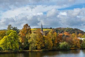 Die Mosel mit herbstlich gefärbten Weinbergen bei Longuich in der Nähe von Trier.