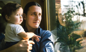 Mature man and baby son looking through window
