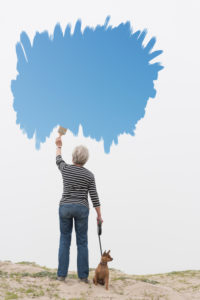 Senior woman with dog on lead painting blue sky in air